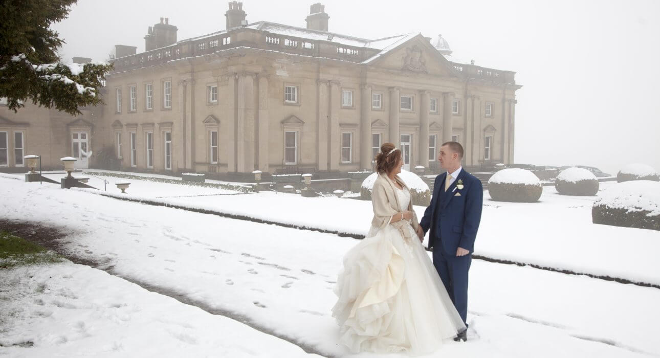Married couple in snow in the grounds of Wortley Hall, Sheffield.