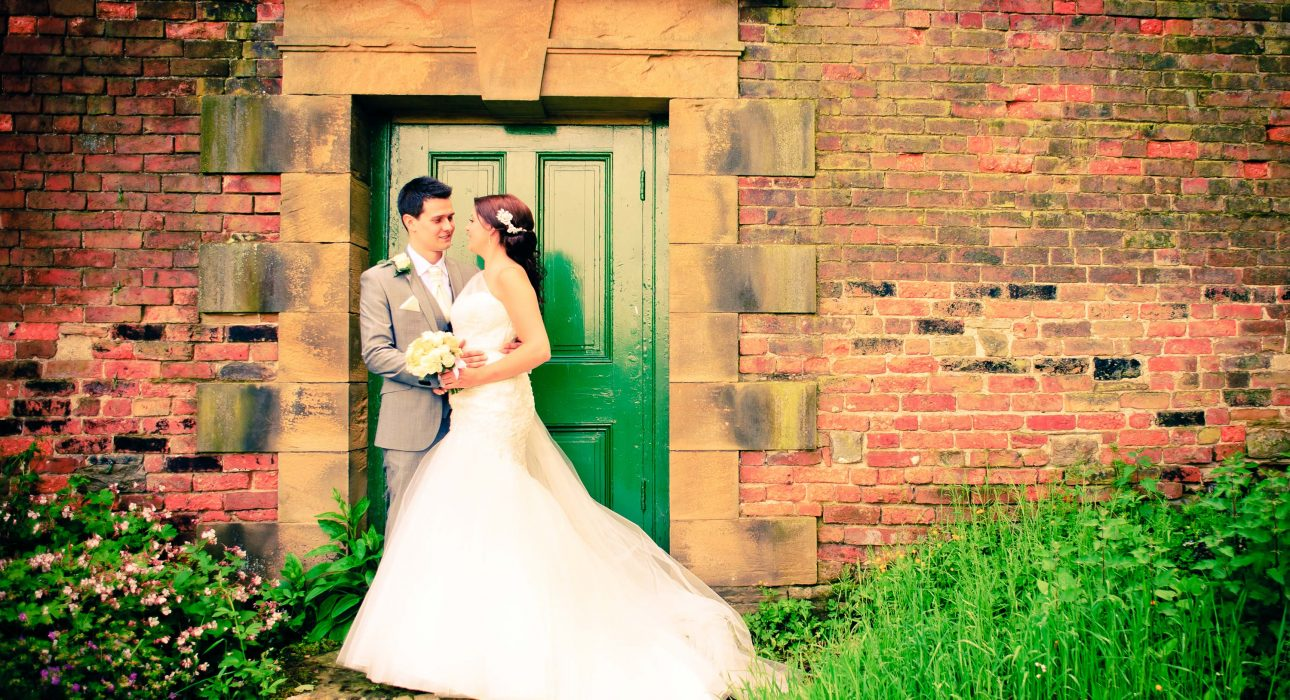 Happy Couple on their Wedding Day at Wortley Hall Standing by a Green Door