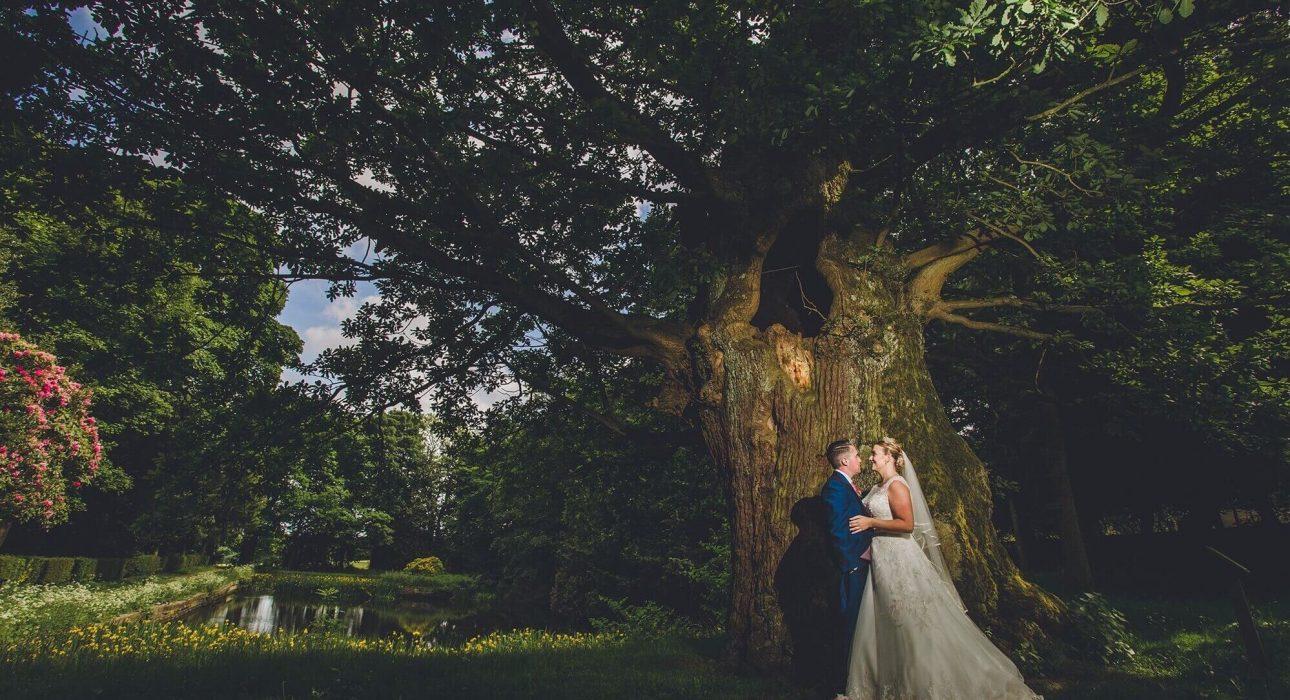 Wedding couple stood under oak tree by pond